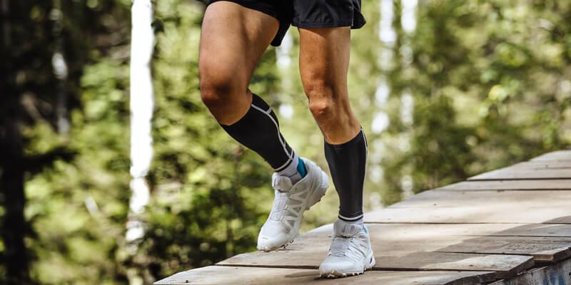 Zlatoust, Russia - August 28, 2016: marathon runner running in forest wooden bridge, feet in compression socks during Mountain marathon